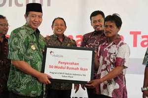 Bupati Tuban, H. Fathul Huda menerima potongan tumpeng tasyakuran program CSR Apartemen Ikan dari General Manager PT Holcim Indonesia Tbk, Sidik Darusulistyo.